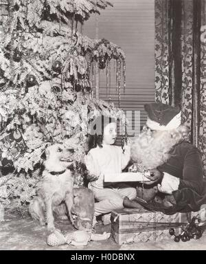 Santa Claus giving gift to little girl and her dog - Stock Image