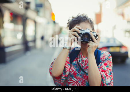 Portrait young woman photographing with camera on street - Stock Image