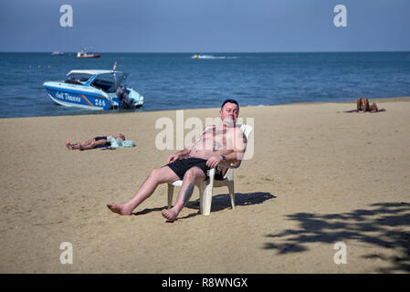 Man sunbathing at the beach, sat on a plastic chair - Stock Image