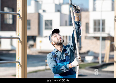 Handsome workman in uniform mounting rope for climbing on the playground outdoors - Stock Image