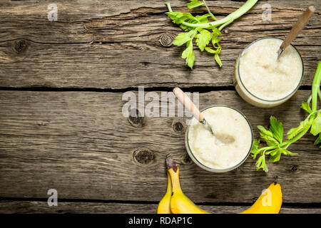 Banana smoothie with celery. On a wooden background. - Stock Image