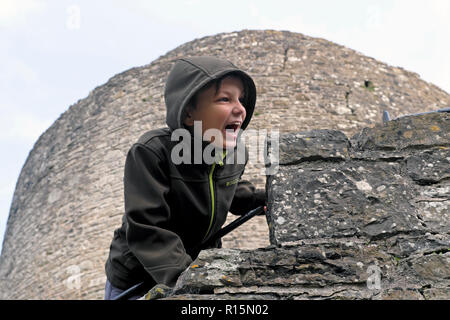 A boy shouting leaning over the edge of a castle wall at Dinefwr Castle in Dinefwr Park Llandeilo, Carmarthenshire South Wales UK  KATHY DEWITT - Stock Image