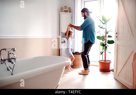 A small girl with young father in bathroom at home, having fun. - Stock Image