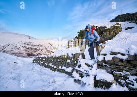 Hiker crossing a stile over a stone wall at Hartsop Above How in the English Lake District. - Stock Image