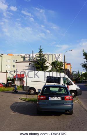 apartment block,auto,automobile,back,blue sky,car,city,day,daytime,license plate,outdoor,parked,poland,polish,poznan,shadow,spot,street,sunny,transpor - Stock Image