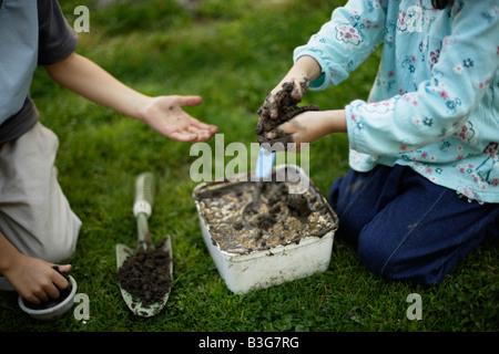 Making mud cakes - Stock Image