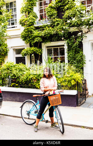 Woman on bike, woman on pushbike, woman cyclist, going on bike ride, trip out on bike, cycle, pushbike, bike, woman, lady, girl, basket on bike, - Stock Image