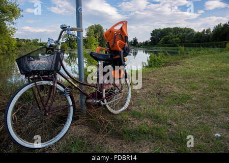 A city bike leaned on pole near a river - Stock Image