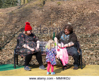 Obese man and woman sitting on a park bench. Blond toddler girl is standing close to them at the Cytadela park in Poznan, Poland - Stock Image