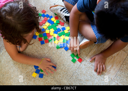 Two children count colored tiles in an elementary school setting. - Stock Image