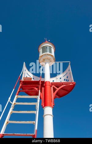 Red and white navigation mark with steps against a blue sky - Stock Image