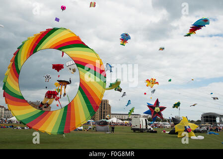Portsmouth, UK. 15th August 2015. A huge rotating kite takes off with a multitude of kites flying in the background - Stock Image