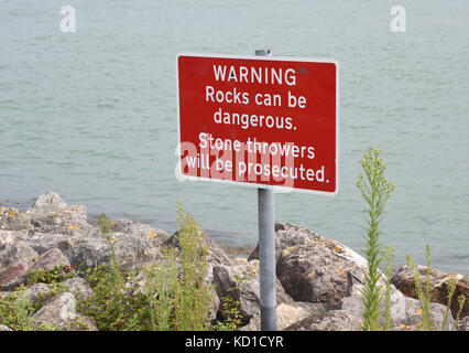 A red warning sign on rocks by the promenade at Southsea. The sign says 'Warning Rocks can be dangerous. Stone throwers - Stock Image