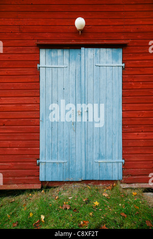 Red house with blue door in autumn - Stock Image