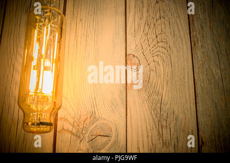 Rope light bulb over weathered wooden background. Low angle view - Stock Image