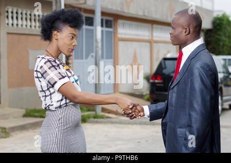 Young businessman introducing himself at a young businesswoman near her home - Stock Image