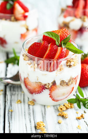 Healthy breakfast of strawberry parfaits made with fresh fruit, yogurt and granola over a rustic white table. Shallow depth of field with selective fo - Stock Image