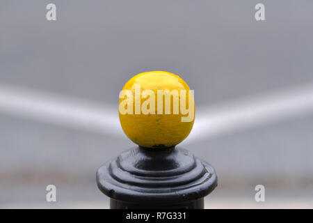 single yellow metal ball on parking pole, blurred street in the background, white lines symmetry - Stock Image