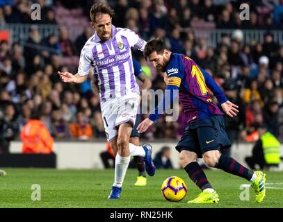 Barcelona, Spain. 16th Feb, 2019. Barcelona's Lionel Messi (R) competes with Valladolid's Michel Herrero during a Spanish league match between FC Barcelona and Valladolid in Barcelona, Spain, on Feb. 16, 2019. FC Barcelona won 1-0. Credit: Joan Gosa/Xinhua/Alamy Live News - Stock Image