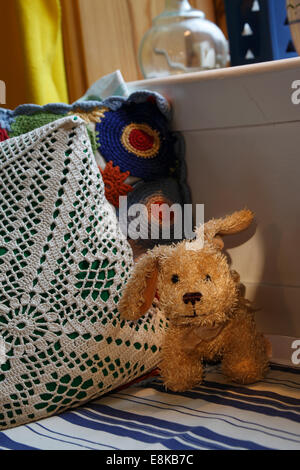 A  plush dog is sitting on a  wooden sofa. - Stock Image
