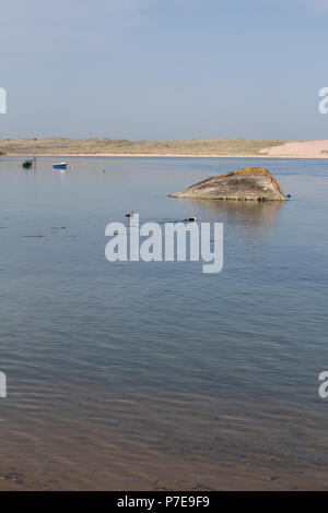 The old shipwreck in the Ythan Estuary, with two small boats in the background, Newburgh, Aberdeenshire, Scotland, UK. - Stock Image