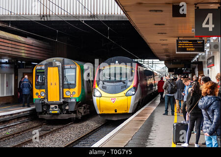 Train approaches Birmingham International Tran Station to pick up passengers on a crowded platform, Birmingham, West Midlands, UK. - Stock Image