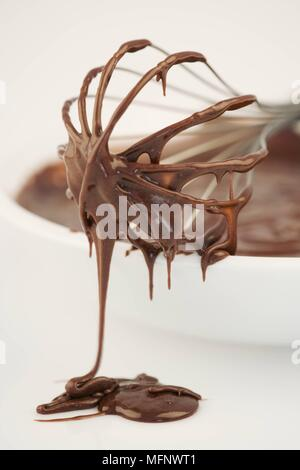 Stainless steel whisk on side of white bowl with chocolate mix. White background. Studio shot.       Ref: CRB538_103609_0021  COMPULSORY CREDIT: Marti - Stock Image