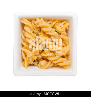 Fusilli pasta cooked with cheese sauce in a square bowl isolated on white background; - Stock Image