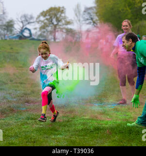 Young girl runner laughing and being covered in paint on Macmillan cancer charity 5K colour fun run. - Stock Image