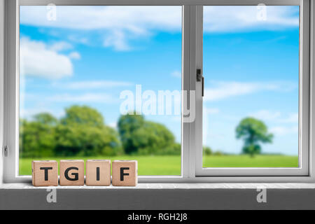 TGIF weekend sign in a white window with a view to sunshine over a beautiful landscape - Stock Image