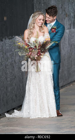 A newly married couple smiling and posing in a loving embrace. The beautiful bride is holding an Autumn bouquet and wearing a white lace wedding dress - Stock Image