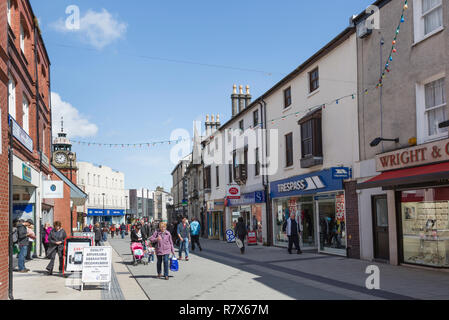 Street scene with people and shops in the city centre shopping precinct. High Street, Bangor, North Wales, UK, Great Britain - Stock Image