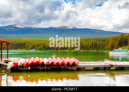 Colorful canoes lie on the dock at Maligne Lake in Jasper National Park, Alberta, Canada. The lake is famous for the surrounding peaks and the three v - Stock Image