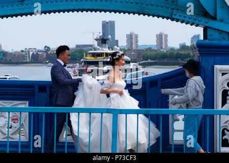 London, England. 4th July 2018. A couple have their wedding photos taken on London's Tower Bridge among all the tourists on another very hot day. The present heatwave is set to continue. ©Tim Ring/Alamy Live News - Stock Image
