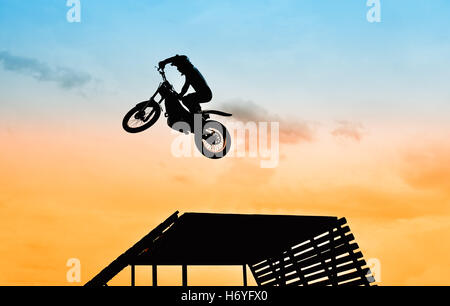 acrobatic jump with motorbike at sunset - Stock Image