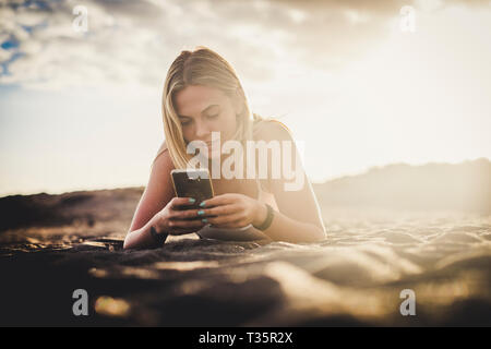 Milennial young beautiful blonde girl type on the phone lay down on the sand at the beach in outdoor nature activty - technology everywhere and intern - Stock Image