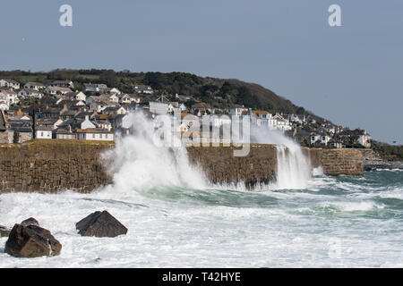 Mousehole, Cornwall, UK. 13th Apr, 2019. UK Weather. Winds of 50mph, and big waves batter the harbour wall at Mousehole this lunchtime. Despite the wind it was still sunny. Credit: Simon Maycock/Alamy Live News - Stock Image