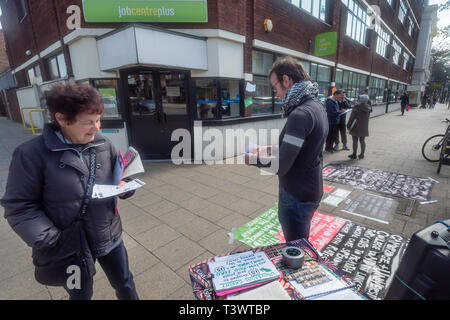 London, UK. 11th April 2019. Activists protested at lunchtime outside Tottenham Jobcentre Plus, speaking and handing out leaflets and talking with passers-by and people entering and leaving the job centre and calling for Universal Credit to be scrapped. They echoed UN rapporteur Philip Alston who talked of the great misery inflicted unnecessarily by the DWP on the working poor, single mothers and those with disabilities. From the start it has been marked by delays and inconsistencies by the DWP and a harsh benefits sanction regime that has unfairly penalised many, causing great suffering, huge - Stock Image