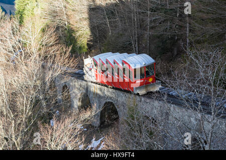 Red car of the old Schlattli-Stoos funicular approaching its top station on a steep viaduct. Stoos, Schwyz, Switzerland. - Stock Image