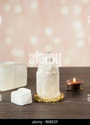 Naturally carved mineral stone Selenite tower has healing on cleansing properties. Candle holder, piece of raw and carved Selenite tower on dark woode - Stock Image