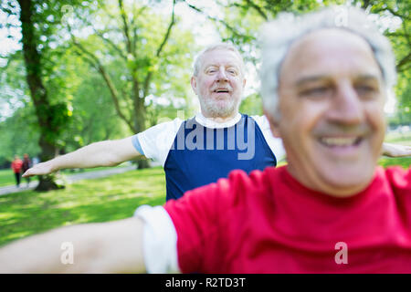 Active senior men exercising, stretching in park - Stock Image