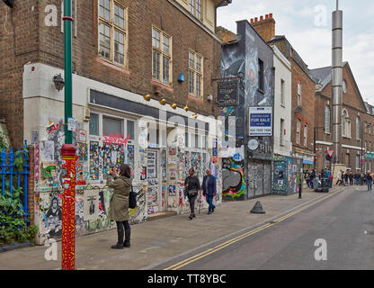 LONDON ENGLAND BRICK LANE PERSON PHOTOGRAPHING  WALL PAINTINGS OR GRAFITTI ON THE WALLS OF A SHOP FRONT - Stock Image