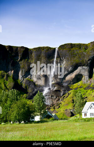 An Icelandic waterfall with house beneath it - Stock Image