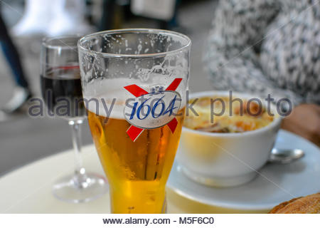 A small lunch at an outdoor sidewalk cafe in Paris France with onion soup, a glass of red wine and a beer. - Stock Image