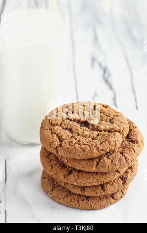 Overhead shot of stack of fresh homemade oatmeal cookies with a bottle of milk on a white table against a white background.. - Stock Image
