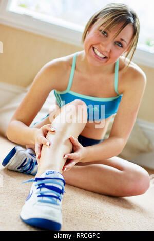 Teen girl sat stretching on the floor - Stock Image