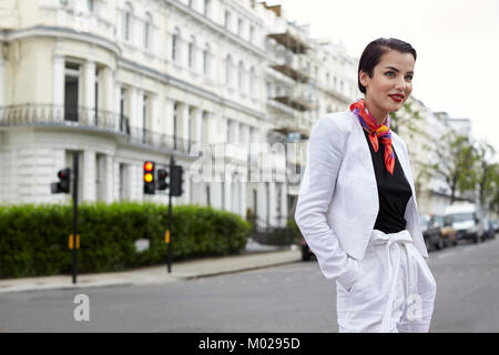 Smiling woman standing in street wearing white linen suit - Stock Image
