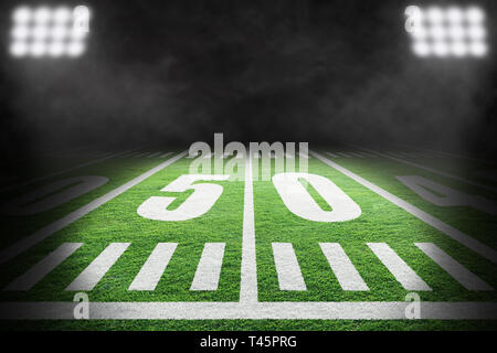 Close up of American football field with stadium spotlight on specific 50 yard markings and background smoke with copy space. - Stock Image