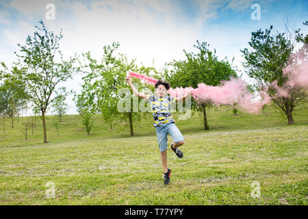 Young boy running trailing a pink smoke flare behind him in a green spring park or garden - Stock Image