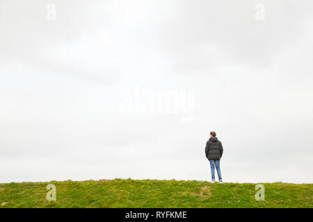 A single person standing on the horizon - Stock Image